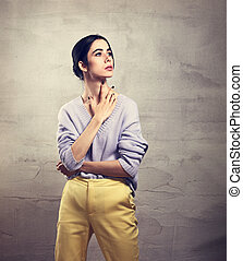 Beautiful young thinking woman posing and looking up with hand on the neck in violet sweater, yellow pants on grey studio background. Portrait of smiling natural european girl. Closeup