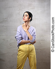 Beautiful young thinking woman posing and looking up with hand on the neck in violet sweater, yellow pants on grey studio background. Portrait of smiling natural european girl.