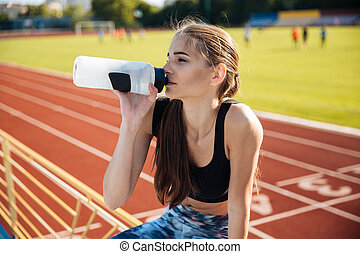 Beautiful young tired fitness girl drinking water after...
