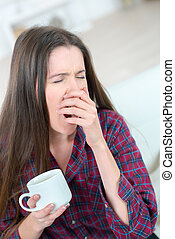 beautiful young tired woman drinking coffee in the morning