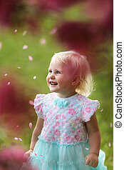 Beautiful Young Toddler Girl Smiling as Flower Petals Fall Off a Crabapple Tree