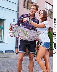 Beautiful young tourist couple with map outdoors