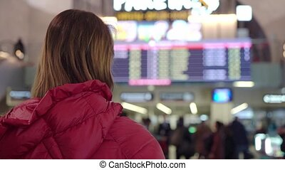 Beautiful young tourist girl in international airport or railway station, near flight information board