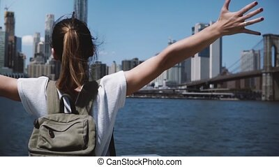 Beautiful young tourist woman with backpack raises arms wide open with joy near Manhattan skyline panorama in New York