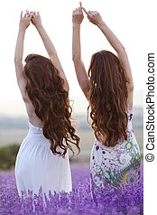 Beautiful young two women over a violet lavender field in Provence at sunset