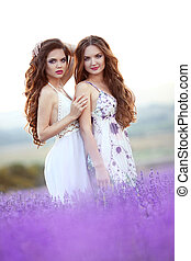 Beautiful young two women over a violet lavender field in...