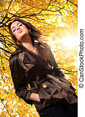Beautiful young under tree branches with yellow autumn foliage in park, blowing a kiss.