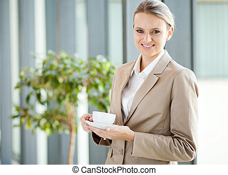 beautiful young white collar worker having coffee during...