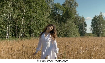 Beautiful young white woman singing with happiness on the field with wheat.