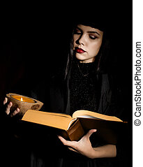 beautiful young witch with a book of spells