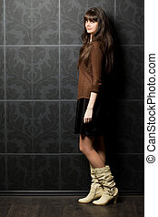 beautiful young woman against wall with pattern, standing sideways, full body