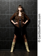 beautiful young woman against wall with pattern, standing widely having placed feet, full body