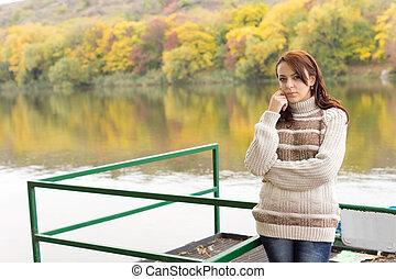 Beautiful young woman alongside a river