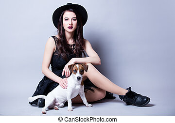 beautiful young woman and her dog sitting in front of wonderful white studio background