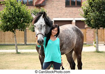 Beautiful young woman and horse near cottage - Beautiful...