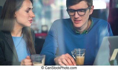 Beautiful young woman and man negotiating in a cafe - modern...
