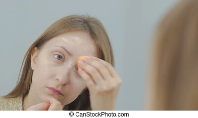Beautiful young woman applies concealer foundation cream make up