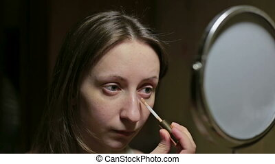Beautiful young woman applies concealer