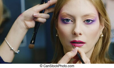 Beautiful young woman apply lipstick on her lips