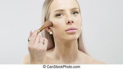 Beautiful young woman applying dry cosmetic tonal foundation...