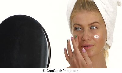 beautiful young woman applying face cream. Close up, bathroom