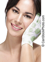 Beautiful young woman applying scrub glove on her perfect skin