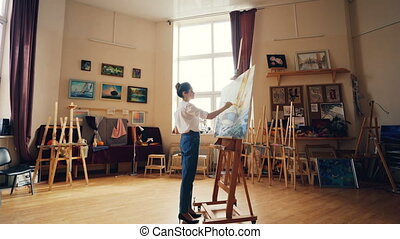Beautiful young woman artist is concentrated on creative...