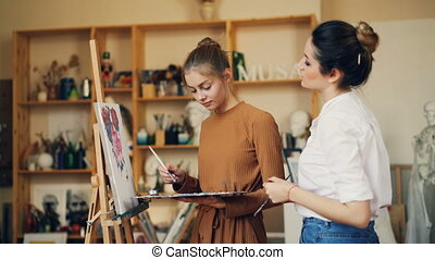Beautiful young woman artist is teaching her student to paint flowers working in studio together with oil paints and palette. Visual arts and youth concept.