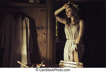 Beautiful young woman at an old rustic cottage