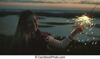 Beautiful young woman at ebening with sparkler, slow motion
