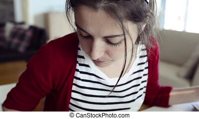 Beautiful young woman at home working on laptop.