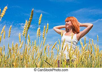 Beautiful young woman at wheat field