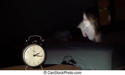 Beautiful young woman awake using smartphone in bedroom at...