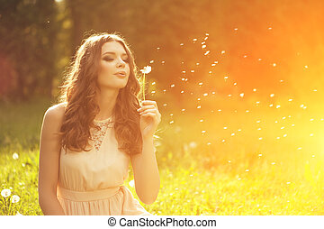 Beautiful young woman blowing a dandelion. Trendy young girl...