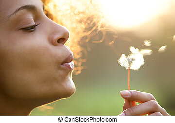 Beautiful young woman blowing dandelion flower