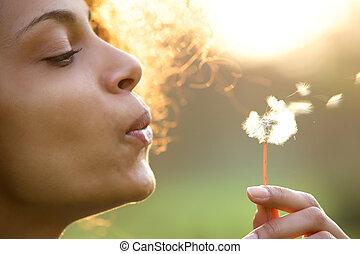 Portrait of a beautiful young woman blowing dandelion flower