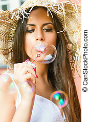 Beautiful young woman blowing soap bubbles outdoor
