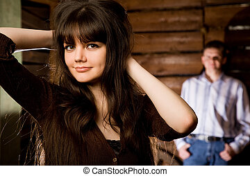 beautiful young woman brunette and young man in wooden log hut, woman standing near wall on background, focus on woman, holding hands behind head