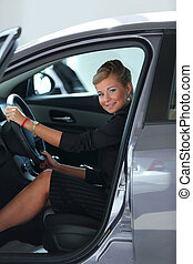 Beautiful young woman buying a car at dealership - Business...