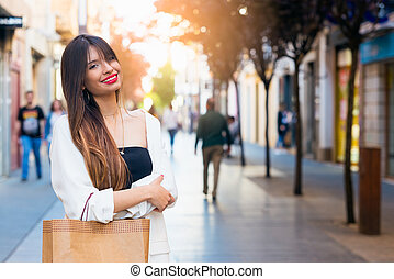 Beautiful young woman buying in comercial street