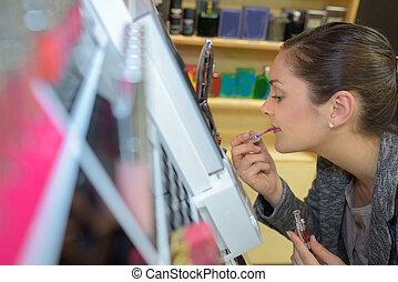 beautiful young woman buying lipstick