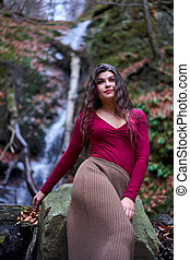 Beautiful young woman by a waterfall