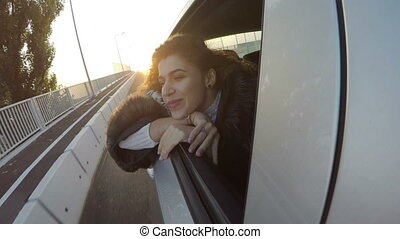 Beautiful young woman celebrating and waving on the window of a car on a bridge