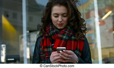 Beautiful young woman chatting on her mobile phone and smiling on camera.