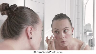 Beautiful young woman checking her face in mirror