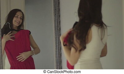 Beautiful young woman checking how pink dress looks on her...