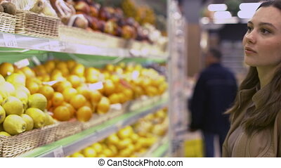 Beautiful young woman chooses lemons in the supermarket
