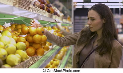 Beautiful young woman chooses oranges and kiwi fruit in a supermarket