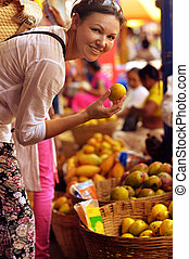 woman choosing fruits on market