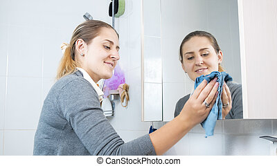 Beautiful young woman cleaning bathroom mirror with blue...